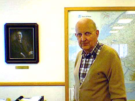 Bernard 'Bud' Bannigan with photo of Michael T. Bannigan, founder, in background.